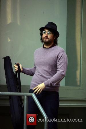 Sean Lennon picks up his guitar to leave after enjoying a cigarette in SoHo with Mark Ronson New York City,...