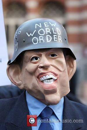 A protester wears a mask of Tony Blair outside Westminster cathedral Protestors were demonstrating against the continued military occupation of...