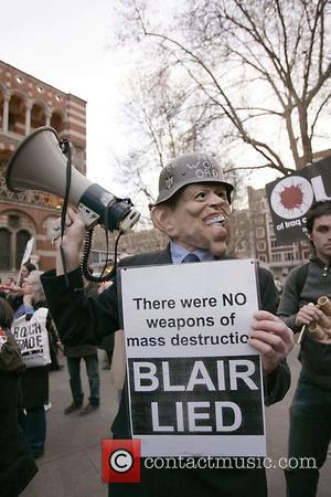A protester wears a mask of Tony Blair and holds a placard outside Westminster cathedral Protestors were demonstrating against the...