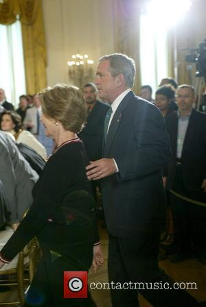 Laura Bush and George W. Bush The signing of HR 5501, the Tom Lantos and Henry J. Hyde United States...