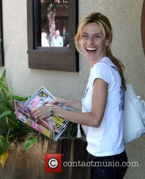 Hayley Rey wife of 'Dr. 90210' Robert Rey holds this week's latest celebrity magazine in Beverly Hills Los Angeles, CA...