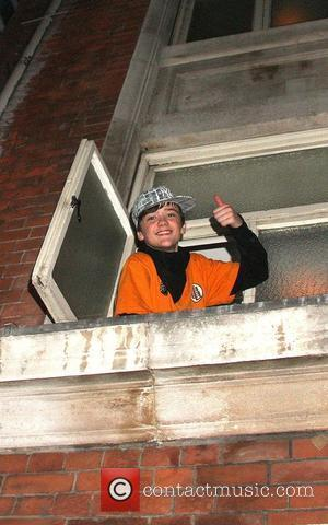George Sampson hangs out of a third floor window to say hello to his many female admirers, following his performance...