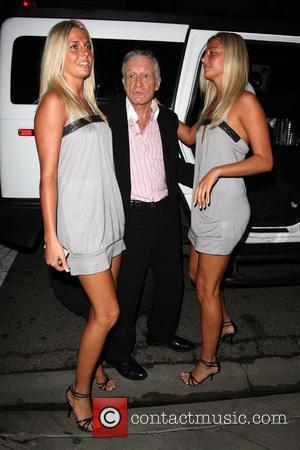 Hugh Hefner with playboy models leaving STK restaurant in West Hollywood with a film crew, recording TV programme 'The Girls...