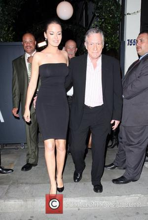 Hugh Hefner and playboy model leaving STK restaurant in West Hollywood with a film crew, recording TV programme 'The Girls...