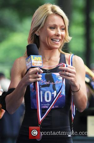 Kelly Ripa ABC's 'Live with Regis and Kelly' presents a medal to the winner of 'High-Heel-A-Thon' in Central Park...