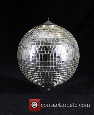 A silver tiled mirror disco ball in its original cardboard box used in the film 'Saturday Night Fever' starring John...