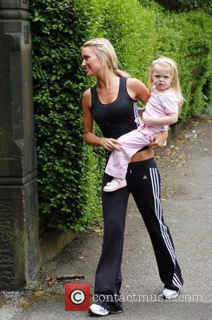 Liverpool WAG Alex Curran holding her daughter Lexie in her arms after visiting her husband at the Melwood training ground....