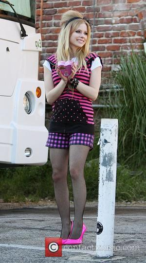 Avril Lavigne, steps out with a beehive hairdo, black fishnet stockings, and 3-inch pink heels while filming a photo shoot...