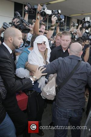Britney Spears, With A Minnie Rose White Shawl On Her Head and Is Met By A Frenzy Of Photographers As She Arrives At Lax Airport On An American Airlines Flight From New York.