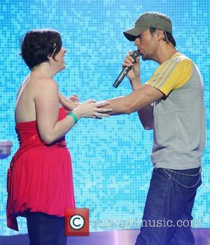 Enrique Iglesias  brings fan Jamie Lee Quinn onstage during a performance at the o2 Dublin for the Cheerios Childline...