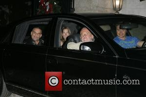 Fashion designer Christian Audigier and wife Ira Audigier smile for the cameras in the back of their Mayback as they...