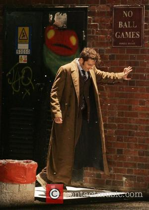 David Tennant looks in distress as he leans against a wall whilst filming a scene in the snow for the...