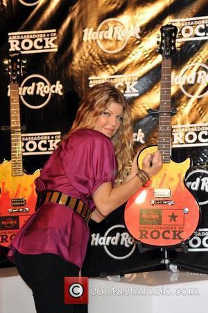 Fergie aka Stacey Ferguson autographs a guitar during an appearance at the Seminole Hard Rock Hotel and Casino to donate...