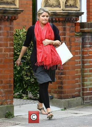 Holly Willoughby leaving her house on her way to film 'Celebrity Juice', concealing her baby bump with a red scarf...
