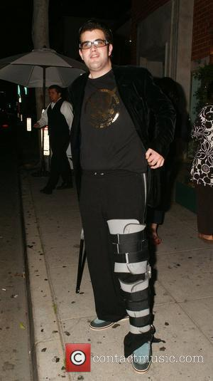 Jason Davis shows off his new line of T-shirts as he leaves a restaurant in Hollywood with a broken leg...