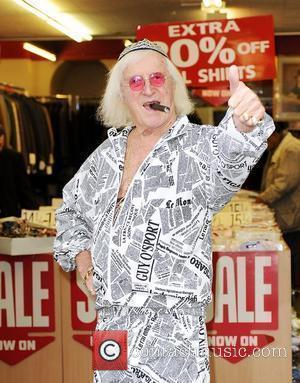 Sir Jimmy Savile poses at Gold's Factory Outlet where he wore a suit to help promote the store's deal of...