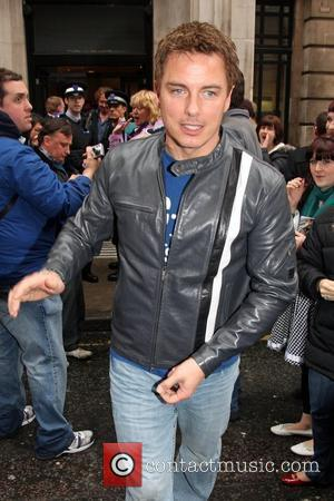 John Barrowman  signs autographs for waiting fans as he leaves the BBC Radio Two studios. London, England - 11.04.09