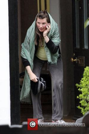Jools Oliver Leaves home covering her head against the wet weather looking very pregnant to visit a private Obstetric clinic...