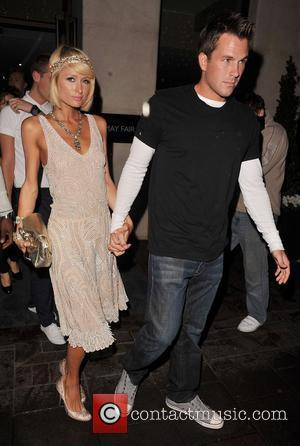 Paris Hilton leaves her hotel with her boyfriend Doug Reinhardt. Paris was wearing a flapper-style dress inspired by the Roaring...