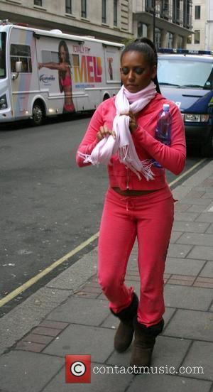 Melanie Brown walks past her promotional van wearing a pink tracksuit on her way to a restaurant during a break...