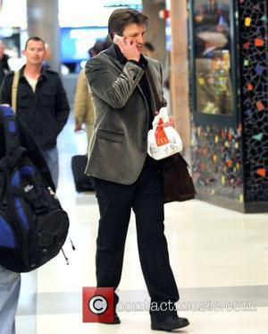 Nathan Fillion, Star Of The New Tv Series 'castle', Talking Into His Cellphone and Carrying A Meal From Mcdonalds At Lax Airport