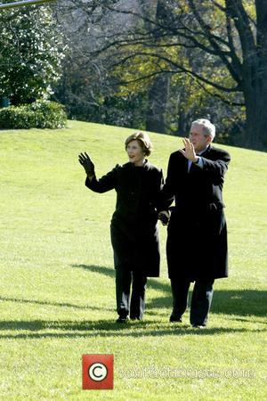 First Lady Laura Bush and President George W. Bush President George W. Bush returns from Camp David where he celebrated...