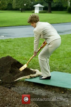 First Lady Laura Bush  holds a shovel as she participate in a commemorative tree planting on the South Lawn...