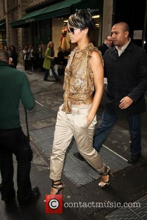 Rihanna, wearing a brown snakeskin top, strappy high heels and leaves the Metropolitan Tower in Midtown Manhattan