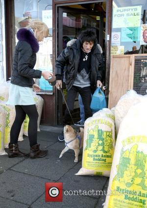 Ekaterina Ivanova and Ronnie Wood  take their dog with with them to visit a pet shop.  Ronnie wood...