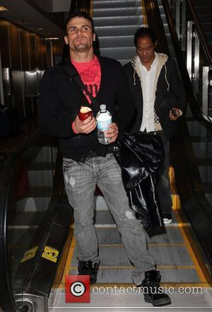 Jeremy Jackson eating an apple and carrying a large bottle of water while arriving at Salt Lake City airport for...