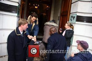 Howard Donald and Mark Owen of Take That sign autographs for waiting fans as they arrive at a restaurant in...