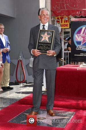 George Hamilton  poses with a plaque after being honored on the Hollywood Walk Of Fame. Hollywood, California - 12.08.09