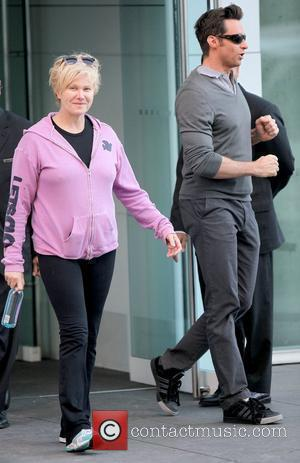 Deborra-Lee Furness and Hugh Jackman Hugh Jackman greets a doorman while leaving his Manhattan residence with his wife New York...