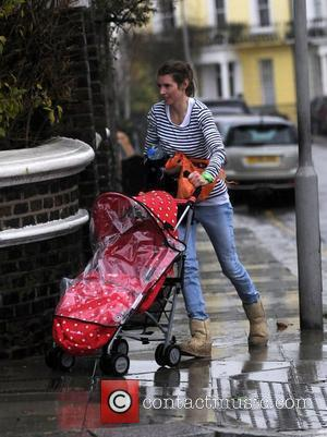 Jools Oliver gets caught in the rain as she pushes her pram from the car into her house London, England...