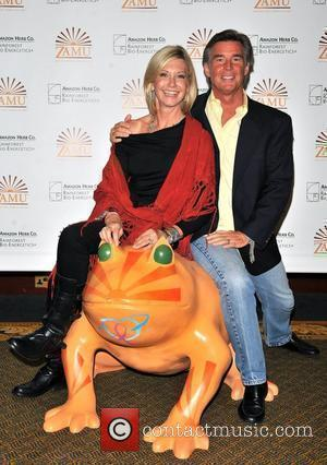 Olivia Newton-john and Her Husband John Easterling Aka Amazon John Pose With A Fiberglass Frog Statue Designed By Olivia In Support Of The Prince's Rainforests Project.