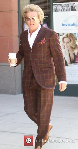 Rod Stewart  was spotted getting a Starbucks coffee in a brown suit in Beverly Hills Los Angeles, California, USA...