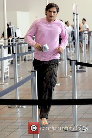 Ashton Kutcher running barefoot on the set of his new film 'Valentine's Day' shooting on location at LAX Los Angeles,...