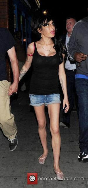 Amy Winehouse was spotted out and about in Camden with some male companions and her security London, England - 02.08.10