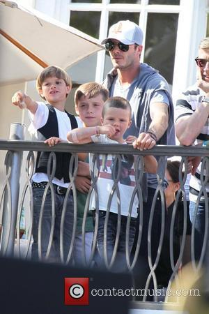 David Beckham with his sons Cruz, Romeo and Brooklyn watch the Jonas Brothers perform live at The Grove from a...
