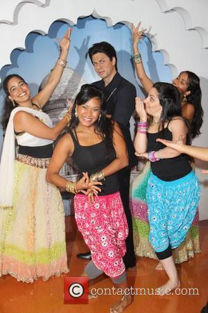 A troupe of Bollywood Axion dancers pose with the wax figure of Indian film star Shah Rukh  The waxwork...