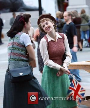 Extras dressed in period clothing chat to each other