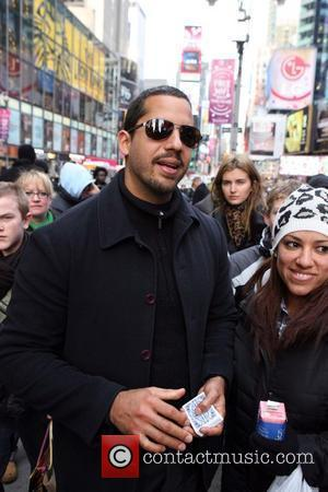 David Blaine performs card tricks in Times Square for tourists and passers by in order to raise money for the...