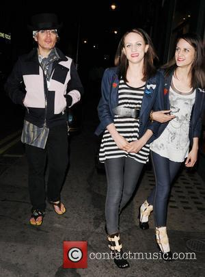 Adam Ant wearing flip flops, bandana a and short top hat leaves Groucho club with two female companions London, England...