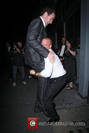 Heston Blumenthal lifting up a friend and breaking his glasses in the commotion,  outside the Groucho Club. London, England...