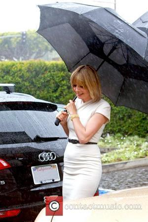 Heidi Klum and Holding A Large Black Umbrella
