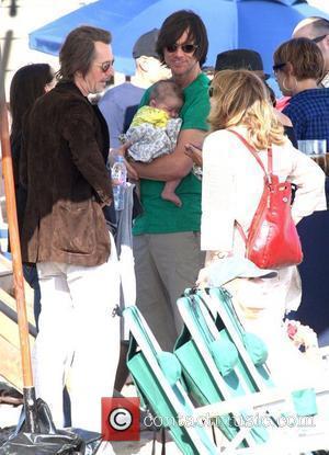 Jim Carrey holding his grandson Jackson Santana while talking to Gary Oldman on Malibu Beach Malibu, California - 04.07.10