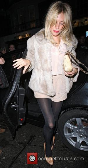 Sienna Miller leaving C London restaurant. Sienna wore a fur coat, bright red lipstick and grey nail varnish London, England...
