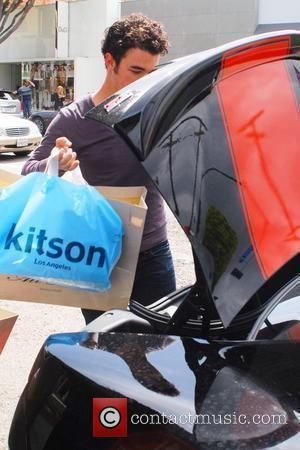 Kevin Jonas loads shopping bags in his car after going on a shopping spree with his wife at Kitson and...