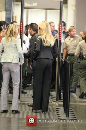Dina Lohan passes through the metal detector at The Beverly Hills Courthouse as her daughter Lindsay begins her 90 day...