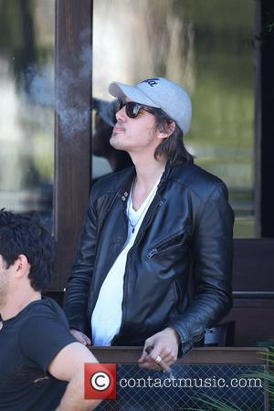 Lucas Haas playing chess with a friend a smoking cigars outside a bar in West Hollywood Los Angeles, California -...